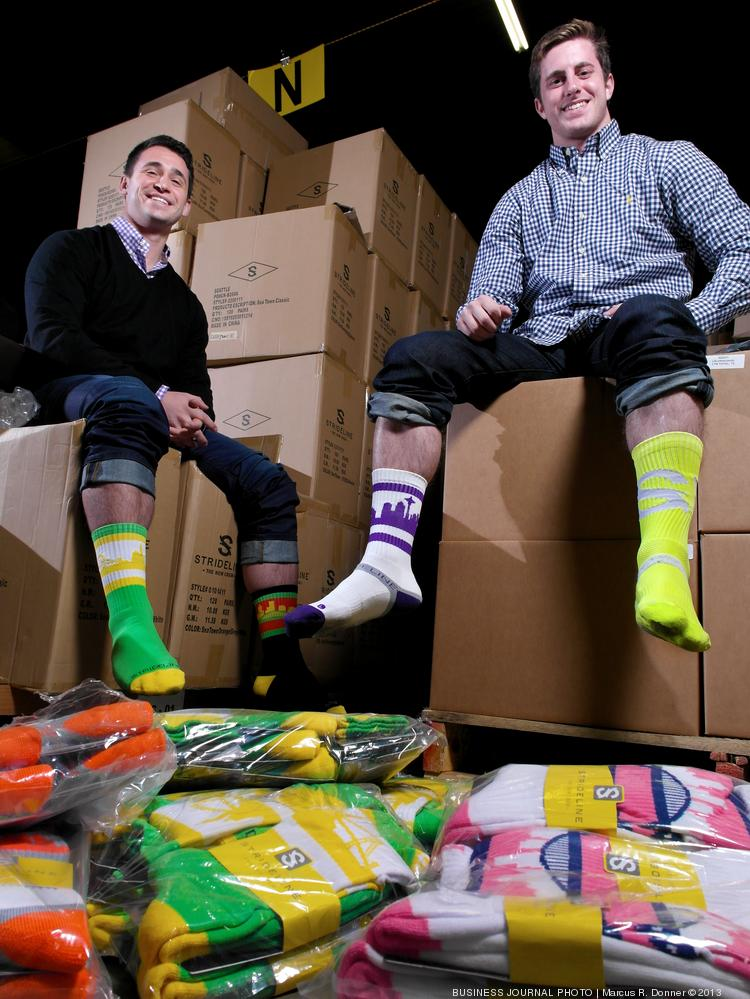 From left, Riley Goodman and Jake Director, co-founders of Strideline, are surrounded by a warehouse of the colorful city skyline socks made by their company.