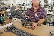 Barry Till, a 30-year employee at the Resource Center, works on a government contract gluing cargo bag straps into position for sewing. Hundreds are employed at the agency's sheltered workshops and worksites.