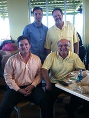 Robby Tebow, standing left, takes a quick break from lunch to pose for a photo with PDQ managing partner for Northeast Florida Todd Alley and Sleiman Enterprises director of asset management Jonathan Heldenbrand and CEO Toney Sleiman (seated).