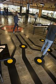 """Black lines link the multiple food vendors to the center of the dining room and a sign that encourages everyone to """"eat."""""""