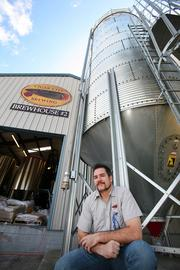 Joey Redner, owner, outside Brew House II with the bulk silo where 2-row malted barley is stored.