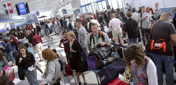 Travelers wait in line to check in for flights at O'Hare International Airport.