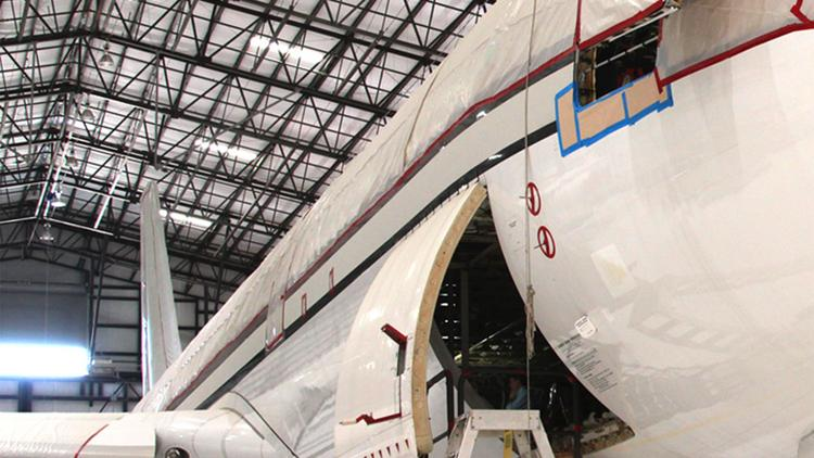 A Gore Design employee conducts work on a plane in the company's Port San Antonio hangar. Gore has changed its name to GDC Technics to reflect a strategic shift.