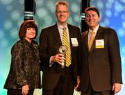 Tracy Crump, executive director of Georgia CIO Leadership Association, from left, presents John Seral with the Lifetime Achievement award along with Damian Artt with Polycom.