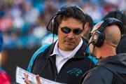 Carolina Panthers head coach Ron Rivera consults with an assistant.