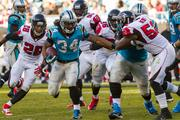 Panthers running back DeAngelo Williams is pursued by defenders Thomas DeCloud, Travian Robertson, Jonathan Massaquoi and Akeem Dent.