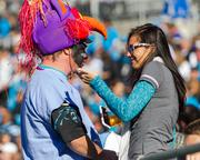 Two Carolina Panthers fans share a light moment as victory seems sure.
