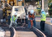 Workers complete track upgrades at the Winter Park train station site. Using existing track corridors saves money and time in the development of the SunRail system.