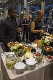 Guests at the grand opening of Charlotte's new Bentley dealership socialize and enjoy hors d'oeuvres.