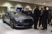 Guests at the grand opening of Charlotte's new Bentley dealership mingle while surrounded by the current lineup of luxury vehicles.