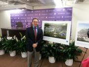 Adam Barrett stands in front of a panel showing the plans for the new Crandon Park Tennis Center.
