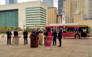 Dallas city officials and dignitaries stand near a D-Link bus Monday at the kickoff for the free bus service to tourist locations.