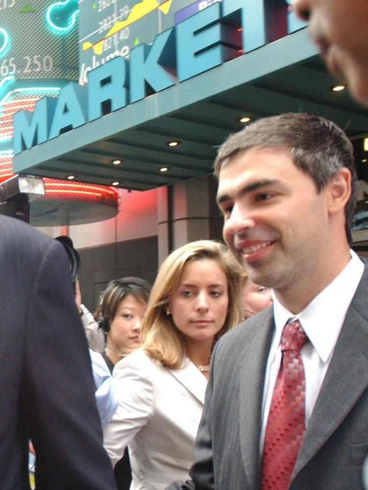 Larry Page, right, co-founder of Google Inc. leaves the NASDAQ Marketsite in the Times Square area of New York, after the opening of the market on August 19, 2004.