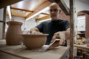 Potter Mark Connolly places a just-thrown bowl on a shelf to dry in the pottery studio at the Red Wing Pottery Co. in Red Wing.