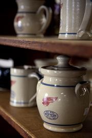 Finished pieces of pottery bearing the Red Wing Pottery Co. logo sit on shelves in the company's showroom in Red Wing.