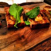 Grilled Wild Rice Toast with uni butter and chorizo on cedar plank