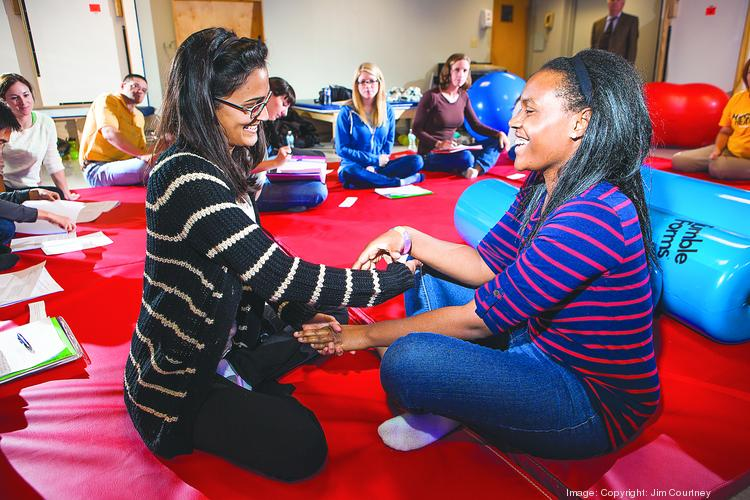 Monal Shah, left, and Vanessa Armstrong are candidates for master's degrees in occupational therapy at D'Youville College. Here, they demonstrate the exercise used for a patient they worked with during a clinical session. The college has seen a huge boost in enrollment for health-care programs in recent years.
