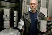 Cell System Operator James Spencer holds a solid block of aluminum (right) and the nearly finished Boeing 777 part (left) after it's machined by the system.