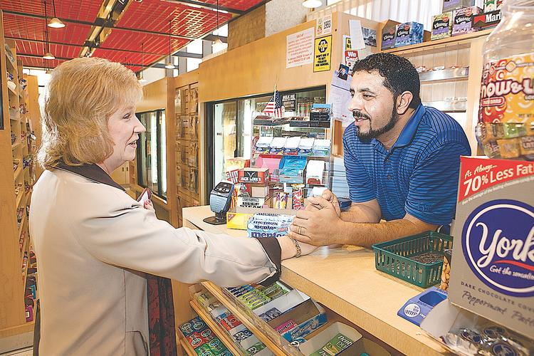 """Ahmed al Hadhari chats with Vicki Barbus, an HSBC administrative assistant who used to work in One Seneca Tower but still comes to visit his newsstand several times a week. On the day this photo was taken, al Hadhari said he had just """"20 or 25 customers"""" all day."""
