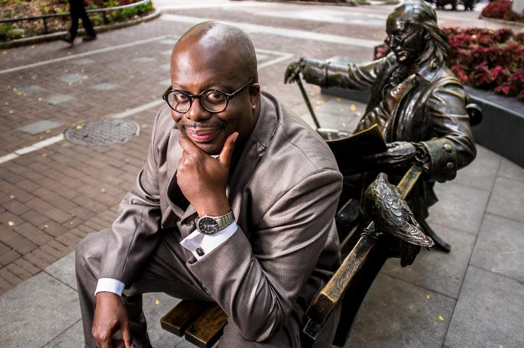 Chad Dion Lassiter, president of the  Black Men at Penn, on the University of Pennsylvania campus sitting by the Ben Franklin statue.
