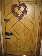 The front door of the manor is detailed with rustic bolts.