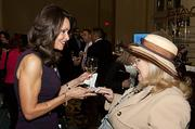 Liz Brunner of Brunner Communications exchanges business cards with Linda Samuels of Billionaire Babies at the Boston Business Journal's Power 50 event at the Boston Harbor Hotel.