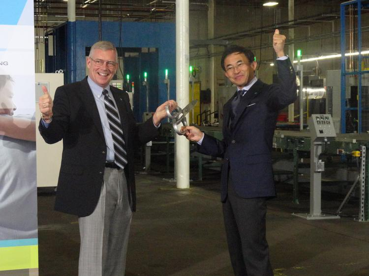 David Swift, (left) the CEO and president of Goodman and the head of Daikin's North American operations, and Takeshi Ebisu, a senior executive officer and a member of Daikin's board, cut a ribbon at the Daikin manufacturing line in Houston.