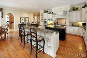 11235 Hunters Pond Road: The breakfast and hearth rooms flow into the kitchen, which features custom counters and top-of-the-line appliances.