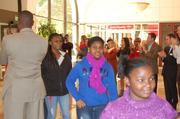 Guests applaud the arrival of a busload of Byers Elementary pupils for their first meeting with Mentors in the Beyond School Walls program.