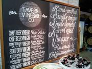 The variety of vinegars available is highlighted on a menu board.