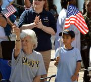 Irmtraud Pflieger, left, and Jacob Dobeson, right, wave American flags to the groups and organizations marching on the Water Street during the Jacksonville's Veterans Day Parade on Monday, Nov. 11, 2013.