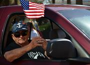 A participant of the Jacksonville's Veterans Day Parade waves the American flag during the Jacksonville's Veterans Day Parade on Monday, Nov. 11, 2013.