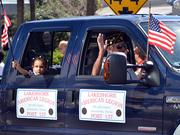 Memebers of the Lakeshore American Legion Post 137 ride in a pickup truck during the Jacksonville's Veterans Day Parade on Monday, Nov. 11, 2013.