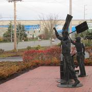 A statue of Boeing strikers, in front of the Machinists' Everett offices, frame the Boeing assembly plant in the background.