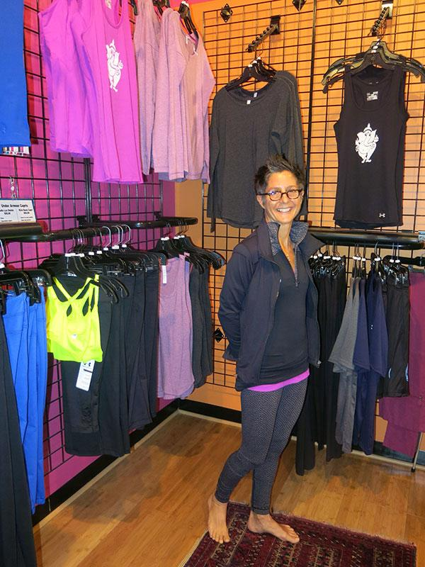 Kim Manfredi, co-owner of Charm City Yoga, in front of a rack of Under Armour apparel at the studio's Mount Vernon location. Charm City Yoga instructors wear Under Armour clothes as part of a deal to test the company's latest products.