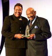 Erica Qualls, GM of Marriott Marquis, presents Herman Russell with an award for being inducted into the ACVB Hospitality Hall of Fame.