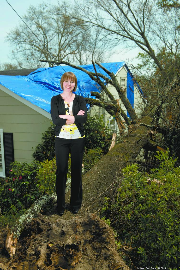 Meredith Jones with Jones-Warren Construction, stand atop a tree toppled by this weeks storms. Her company is making the repairs to the house.