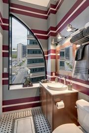 Soo Line Building City Apartments bathrooms have 36-inch soaking tubs with subway-tile surrounds, tile floors, adjustable-height rainshower heads, marble vanities, curved shower rods, deep-drawer storage, towel shelves and custom-framed mirrors and medicine cabinets.