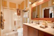 Soo Line Building City Apartments master bathrooms have standing showers, subway-tile surrounds, tile floors, adjustable-height rainshower heads, marble vanities, deep-drawer storage, towel shelves and custom-framed mirrors and medicine cabinets.