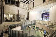 The skyway-connected Soo Line Building City Apartments lobby features a floating glass staircase with a terrazzo floor.