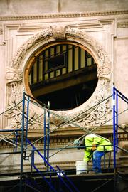 A construction worker below one of the iconic round windows of the Ferninand Building in Roxbury, MA.