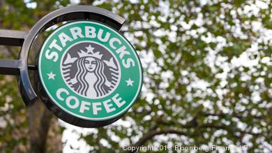 A Starbucks Corp. logo hangs outside one of the company's coffee shops.
