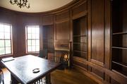 The circular library in the front of the house features rich wood paneling and a cozy fireplace.