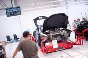 A Model S sedan rolls down an assembly line at Tesla's plant on a robotic carrier called a SmartCart. The robot follows a magnetic strip along the factory floor, ferrying the chassis to each work station.