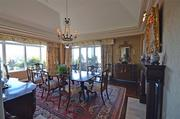 The dining room has river and city views along with vaulted ceilings and hardwood floors. French doors lead to the covered terrace.