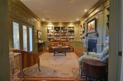 The den/library is outlined in burnished-gold fillet and includes built-in bookshelves.