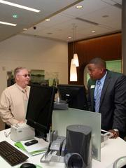 Justin Deskins, branch supervisor at Grow Financial's downtown Tampa branch, helps member, Mike Perry, with a check deposit.