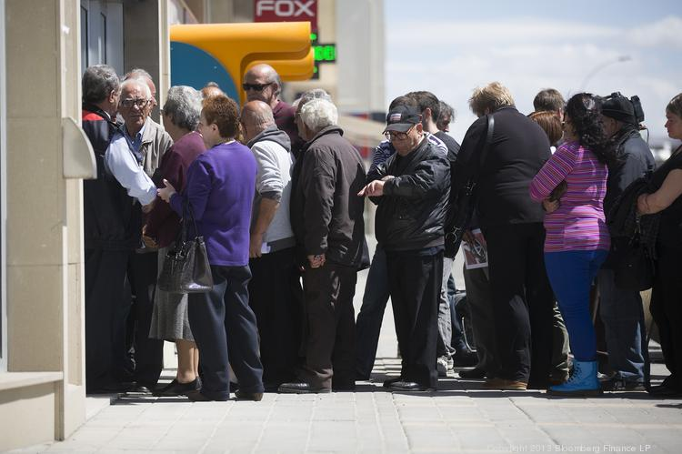 Customers queue outside a Bank of Cyprus Plc branch ahead of opening for the first time in two weeks in Nicosia, Cyprus, on Thursday. The Central Bank of Cyprus's capital controls will include a 300-euro ($383) daily limit on withdrawals and restrictions on transfers to accounts outside the country.