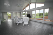 126 Ohmes Road: A 20-by-20 sun room looks out on the yard and the pool.