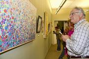 A visitor to the Capital Public Radio art exhibition admires art on display.